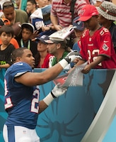 Tampa Bay Buccaneers running back Doug Martin signs a pennant and jersey for a young fan sporting his jersey replica during the 2013 NFL Pro Bowl at Aloha Stadium, Jan. 27. Martin was one of the few rookies to make the Pro Bowl this year.