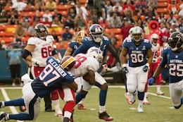 Washington Redskins linebacker Lorenzo Alexander pulls Buffalo Bills running back C.J. Spiller down to the turf during the 2013 NFL Pro Bowl, Jan. 27. The Marines at the Pro Bowl contributed to the festivities with a color guard, stage assistance, a troop formation and a welcoming home for Marines recently returned from deployment at halftime.