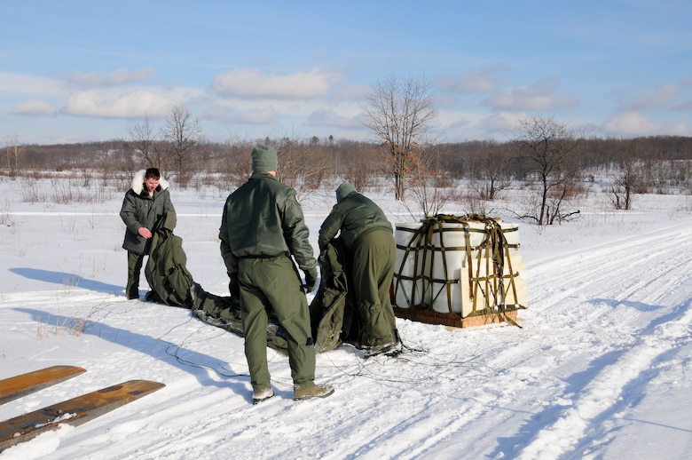 U.S. Air Force Tech. Sgt. Patrick Hann, left, Staff Sgt's James Benham (center) and Joseph Campbell (right), 110th Airlift Wing, 172nd Airlift Squadron recover a cargo drop from C-130's, Grayling Air Gunnery Range, Frederic, Mich., Jan. 26, 2013. Cargo was dropped to certify the range and personnel in ground recovery. (U.S. Air Force photo by Airman Justin Andras/released)