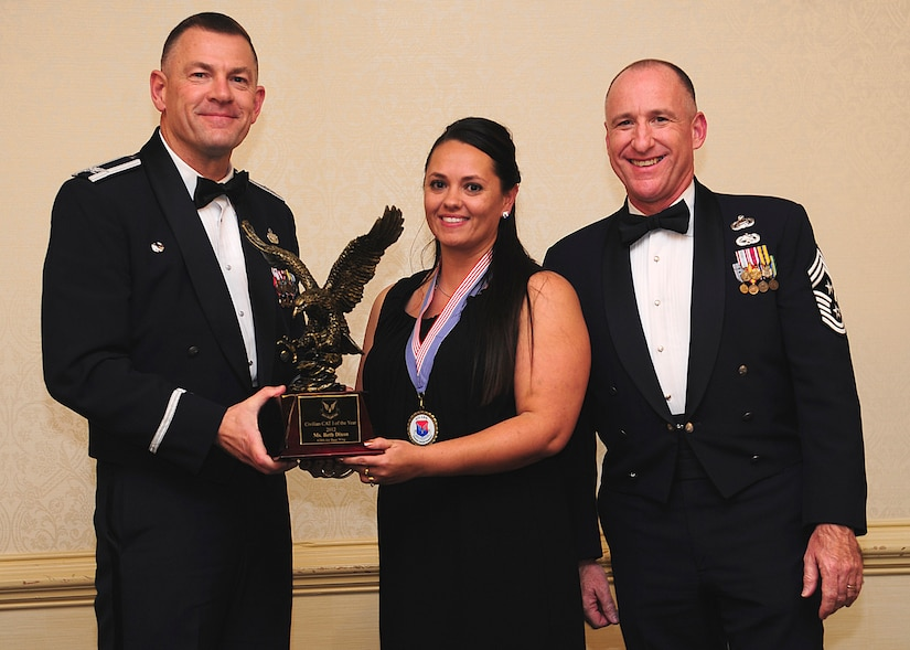 Colonel Richard McComb, Joint Base Charleston commander, and Chief Master Sgt. Al Hannon, 628th Air Base Wing command chief, present the JB Charleston Civilian Category I of the Year award to Beth Dixon, 628th Security Forces Squadron unit program coordinator, during the 628th ABW Annual Awards Banquet held at the Charleston Club, Jan. 25, 2013, at JB Charleston - Air Base, S.C. (U.S. Air Force photo/Staff Sgt. Rasheen Douglas)