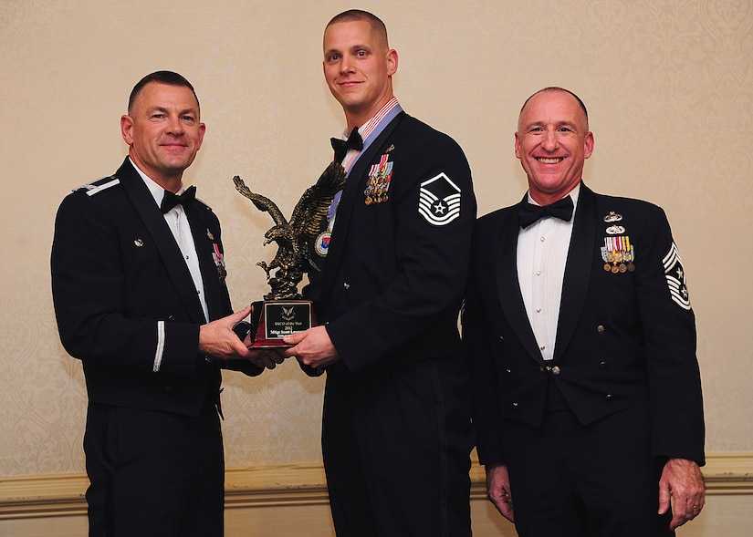 Colonel Richard McComb, Joint Base Charleston commander, and Chief Master Sgt. Al Hannon, 628th Air Base Wing command chief, present the JB Charleston Senior Noncommissioned Officer of the Year award to Master Sgt. Scott Levesque, 628th Communications Squadron plans and programs flight superintendent, during the 628th ABW Annual Awards Banquet held at the Charleston Club, Jan. 25, 2013, at JB Charleston - Air Base, S.C. (U.S. Air Force photo/Staff Sgt. Rasheen Douglas)
