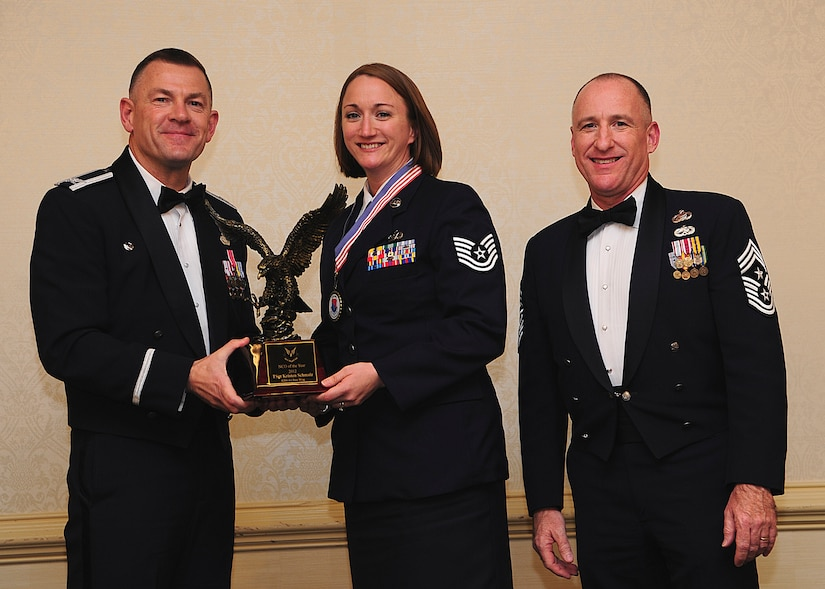 Colonel Richard McComb, Joint Base Charleston commander, and Chief Master Sgt. Al Hannon, 628th Air Base Wing command chief, present the JB Charleston Noncommissioned Officer of the Year award to Tech. Sgt. Kristen Schmalz, 628th Air Base Wing noncommissioned officer in charge of command post operation, during the 628th ABW Annual Awards Banquet held at the Charleston Club, Jan. 25, 2013, at JB Charleston - Air Base, S.C. (U.S. Air Force photo/Staff Sgt. Rasheen Douglas)