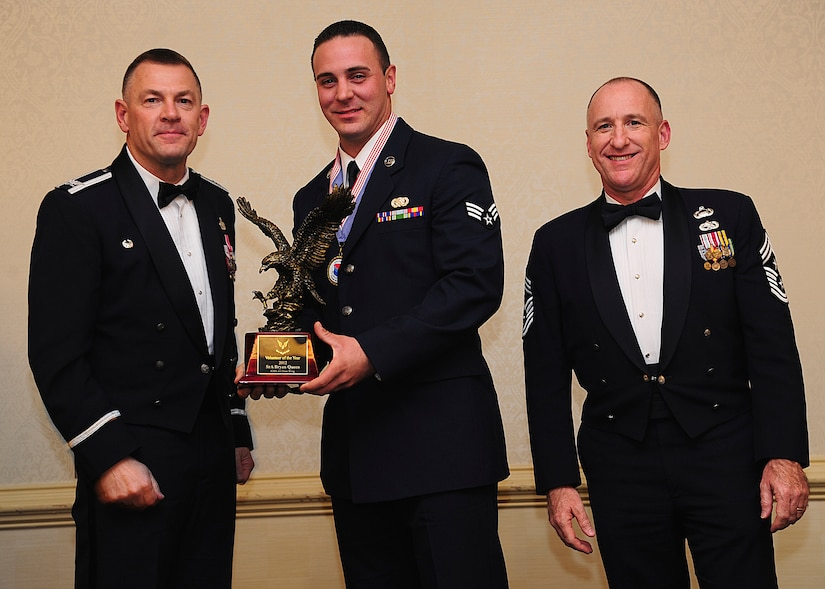 Colonel Richard McComb, Joint Base Charleston commander, and Chief Master Sgt. Al Hannon, 628th Air Base Wing command chief, present the JB Charleston Volunteer of the Year award to Senior Airman Bryan Queen, 628th Logistics Readiness Squadron fuels fixed facility supervisor, during the 628th ABW Annual Awards Banquet held at the Charleston Club, Jan. 25, 2013, at JB Charleston - Air Base, S.C. (U.S. Air Force photo/Staff Sgt. Rasheen Douglas)