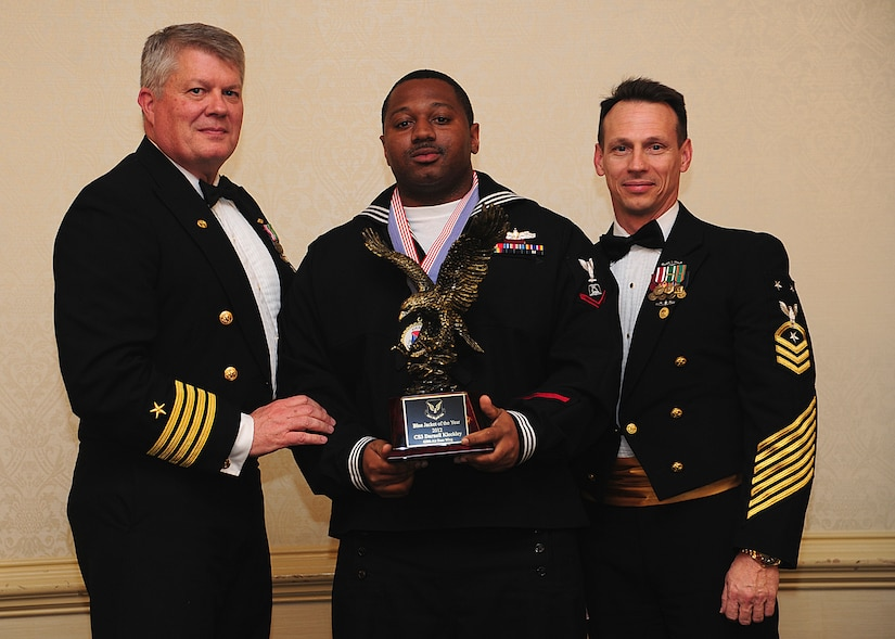 Navy Captain Thomas Bailey, Joint Base Charleston deputy commander, and Master Chief Petty Officer Billy Cady, JB Charleston – Weapons Station command master chief, present the Blue Jacket of the Year award to Petty Officer 3rd Class Darnell Kleckley, Naval Support Activity culinary specialist, at the 628th Air Base Wing Annual Awards Banquet held at the Charleston Club, Jan. 25, 2013, at JB Charleston - Air Base, S.C. (U.S. Air Force photo/Staff Sgt. Rasheen Douglas)