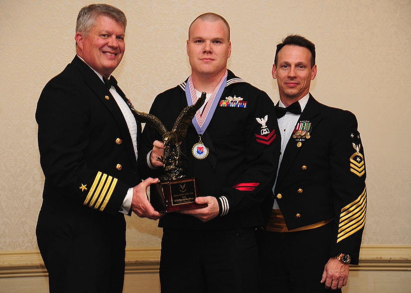 Navy Captain Thomas Bailey, Joint Base Charleston deputy commander, and Master Chief Petty Officer Billy Cady, JB Charleston – Weapons Station command master chief, present the Junior Sailor of the Year award to Petty Officer 2nd Class David Haeffner, Naval Support Activity culinary specialist, at the 628th Air Base Wing Annual Awards Banquet held at the Charleston Club, Jan. 25, 2013, at JB Charleston - Air Base, S.C. (U.S. Air Force photo/Staff Sgt. Rasheen Douglas)
