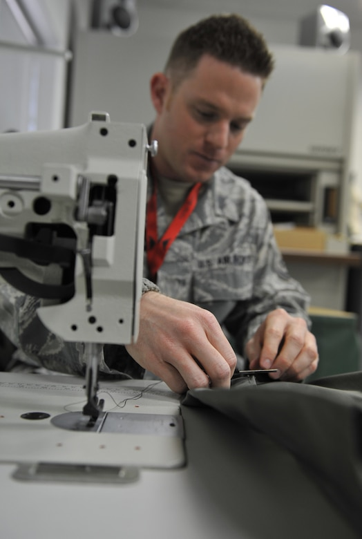 WHITEMAN AIR FORCE BASE, Mo. -- Master Sgt. Jacob Mann, 110th Bomb Squadron, Air National Guard, trims excess thread after sewing an integrated prototype cot, Jan. 18. Pilots use cots in the B-2 Spirit and other aircraft during long-duration flights. (U.S. Air Force photo/Heidi Hunt) (Released)