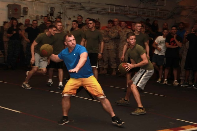 Marines with the 15th Marine Expeditionary Unit throw dodgeballs at their opponents during a dodgeball tournament held in the hangar bay of the USS Peleliu, Jan. 24. The dodgeball challenge was the eighth competition of the Campbell Cup, a bi-monthly challenge that pits teams within the 15th Marine Expeditionary Unit and Peleliu Amphibious Ready Group against each other. The 15th MEU is deployed as part of the Peleliu ARG as a U.S. Central Command theater reserve force, providing support for maritime security operations and theater security cooperation efforts in the U.S. 5th Fleet area of responsibility. (U.S. Marine Corps photo by Cpl. John Robbart III/Released)