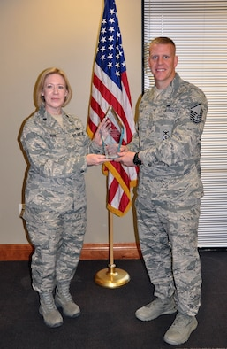 (Right) Master Sgt. Adam Jessee, 926th Security Forces Flight squad leader, receives Air Force Reserve Command's 2012 Outstanding Security Forces Senior Noncommissioned Officer Support Staff award from Lt. Col. Connie Alge, 926th Force Support Squadron commander, here Jan. 31. Jessee was recognized for managing a Regular Air Force standards and evaluation program that certified more than 500 personnel across four units, raising compliance 60 percent. Additionally, he developed a tracking database that processed 233 reports, cutting late reports by 30 percent. Jessee is also certified by the Las Vegas Metropolitan Police Department to instruct personnel on Standard Field Sobriety Tests, among many other accomplishments. (U.S. Air Force photo/Maj. Jessica Martin)
