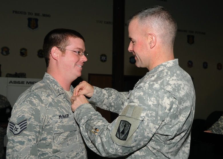 Army Col. Michael Morrissey, commander of the 31st Air Defense Artillery Battalion, Fort Sill, Okla., presents Staff Sgt. Timothy McNary of the Kentucky Air National Guard's 123rd Contingency Response Group with the Army Achievement Medal during a ceremony at Altus Air Force Base, Okla., Jan. 9, 2013. Airmen from Altus; the Kentucky Air National Guard; Charleston Air Force Base, S.C.; Joint Base Lewis-McChord, Wash.; Travis Air Force Base, Calif.; Joint Base San Antonio, Texas; and Westover Air Reserve Base, Mass., provided the timely and safe deployment of Patriot missile batteries and more than two million pounds of equipment to Turkey in support of NATO efforts to augment Turkey's self-defense capabilities. (U.S. Air Force photo by Airman 1st Class Klynne Pearl Serrano)