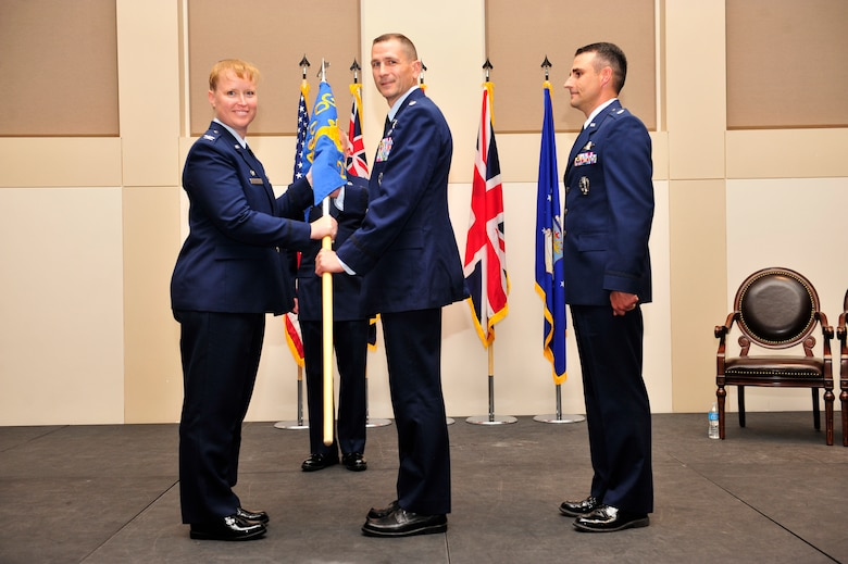 Col. DeAnna Burt, left, 460th Operations Group commander, presents the 2nd Space Warning Squadron guidon to Lt. Col. Francois Roy, middle, 2nd SWS commander, as Lt. Col. John Henley, former 2nd SWS commander stands by June 19, 2013, at the Leadership Development Center on Buckley Air Force Base, Colo. For Roy, this will be his first command of a squadron. (U.S. Air Force photo by Airman 1st Class Darryl Bolden Jr./Released)