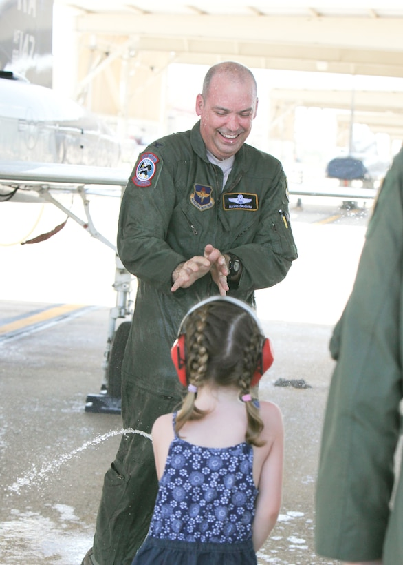 Natalie sprays her dad, Col. David Drichta, 12th Operations Group deputy commander, with water from a fire extinguisher after his first flight back after his battle with cancer at Joint Base San Antonio-Randolph, Texas June 19, 2013.  Drichta was diagnosed with Stage IV cancer in February 2012 and, after more than a year in recovery, was medically cleared to return to flight status.  The flight marked his return to flight status as well as his 3,000th flight hour in Air Force aircraft. (Courtesy photo by Stacy Nyikos)