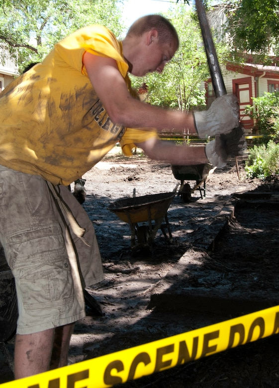 Skyler Cabell clears debris from the front steps of a house in Manitou Springs, Colo., July 2, 2013. Significant rainfall in areas affected by the 2012 Waldo Canyon Fire triggered a flash flood that damaged several homes along the Black Canyon watershed. Cabell, an employee for a local landscaping company, volunteered to help with cleanup efforts. (U.S. Air Force photo/Don Branum)