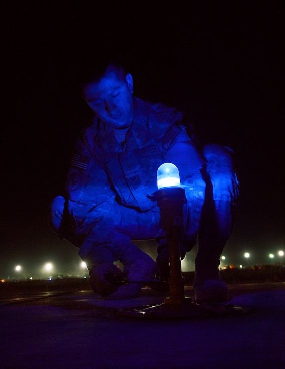 Tech. Sgt. Justin Lotero removes a taxiway light for inspection on Bagram Air Field, Afghanistan, June 6. Lotero, assigned to the 455th Expeditionary Civil Engineer Squadron electrical systems shop, is a member of a three-man airfield lighting team here working every night to maintain more than one-thousand lights spanning over one-million square feet on the flight line. He is deployed from the 117 Air Refueling Wing, Birmingham, Ala. (U.S. Air Force photo/Staff Sgt. Stephenie Wade/Released)