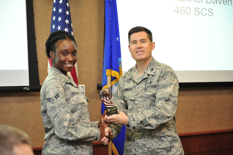 Airmen 1st Class Channel Davenport, 460th Space Communications Squadron, accepts Airmen of the Month Award from Col. Dan Wright, 460th Space Wing commander, July 2, 2013, at Buckley Air Force Base, Colo. Davenport distinguished herself by tracking and accounting for 89 mission critical items valued more than $200,000. She also serves on the Mile High Honor Guard and rendered two military funerals, affording dignity and respect to veterans. (U.S. Air Force photo by Airman 1st Class Darryl Bolden Jr./Released)