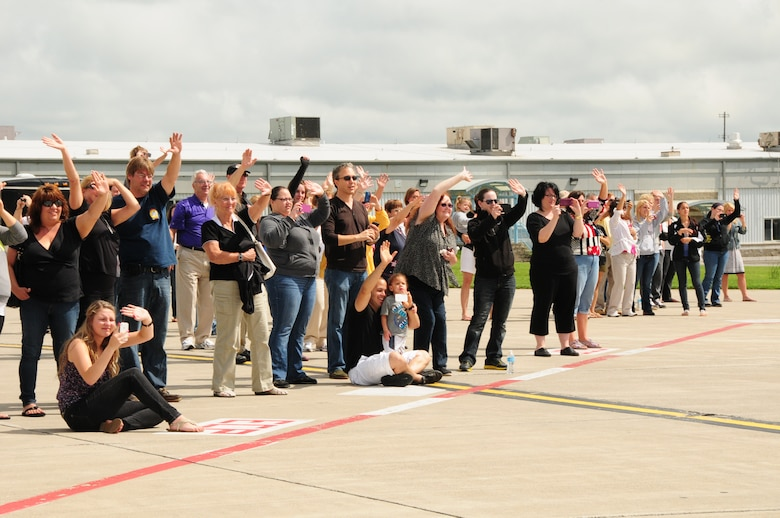 Family and friends of the 107th Airlift Wings members wave good bye as the C-130 departs the Niagara Falls Reserve Station as they deploy to Southwest Asia on June 29, 2013. (Air National Guard Photo/Senior Master Sgt. Ray Lloyd)