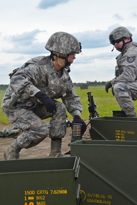 U.S. Air Force Airman 1st Class Courtney Metzger, a security forces member with the 128th Air Refueling Wing, Wisconsin Air National Guard, hurriedly picks up a new case of amunition for an M249 automatic rifle during a heavy weapons qualification course at Hardwood Air-to-Ground Weapons Range, Wis., June 11, 2013.  Members of the 128th Security Forces Squadron continued annual training at Hardwood Range, which is part of the Volk Field Combat Readiness Training Center.   (U.S. Air National Guard photo by Staff Sgt. Jenna Hildebrand/Released)