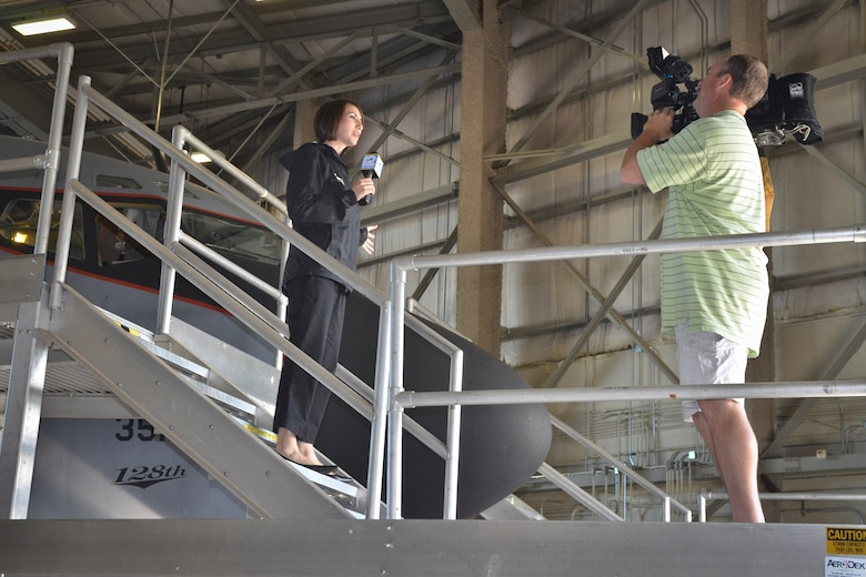 Hillary Mintz of WISN 12 Milwaukee captures her story introduction next to the nose of a KC-135R Stratotanker at the 128th Air Refueling Wing, Wisconsin Air National Guard, June 28, 2013. The Milwaukee news teams were invited to attend a media engagement event at the air wing to learn more about the KC135R flight simulator and phase maintenance of the KC135R aircraft. (U.S. Air Force photo by Senior Master Sgt. Jeff Rohloff/Released)