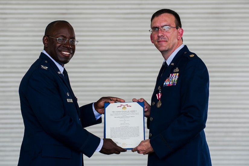 Col. Dennis Dabney, 437th Maintenance Group commander, presents Maj. Matthew Manns, 437th Maintenance Operations Squadron commander, the Meritorious Service Medal certificate during the 437th Maintenance Operations Squadron inactivation ceremony June 28, 2013, at Joint Base Charleston – Air Base, S.C. The 437th MOS was activated in October 2002. (U.S. Air Force photo/ Senior Airman George Goslin)