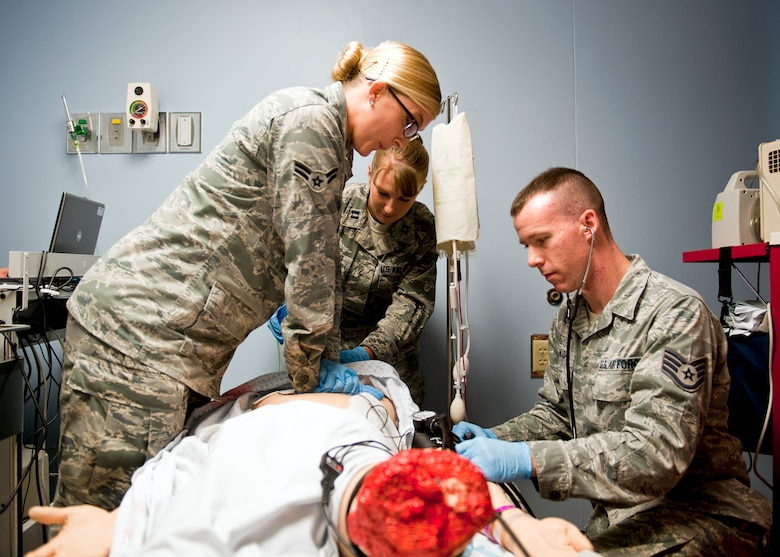 39th Medical Operations Squadron members Airman 1st Class Valerie Essman, ambulance serviceman, Capt. Rachel Rhodes, clinical nurse, and Staff Sgt. Jeremy Canady, medical technician, perform emergency care on a Sim Man medical dummy June 19, 2013, at Incirlik Air Base, Turkey. The Sim Man is capable of simulating various traumas for training purposes. (U.S. Air Force photo by Senior Airman Daniel Phelps/Released)