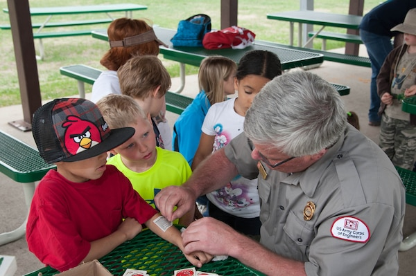 Rich Schueneman, site manager for Lake Ashtabula, near Valley City, N.D., gives temporary water safety tattoos to a group of elementary students that helped plant trees at the park May 16.
