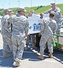 Soldiers with the 601st ASB, CAB, help load a box of donations onto a trailer June 6 at their battalion headquarters for transport to Moore, Okla.  601ST ASB PHOTO.