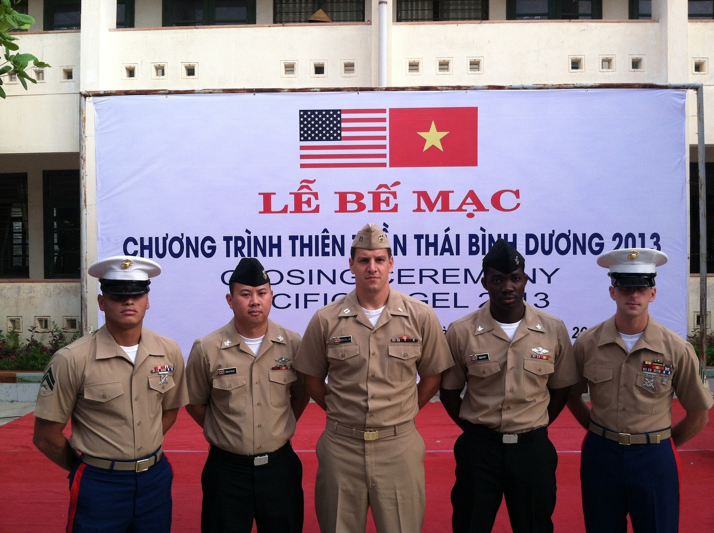 From left to right: Corporal Max Tijerino, 7th Engineer Support Battalion, 1st Marine Logistics Group, Petty Officer 1st Class Lam D. Nguyen, Navy Lt. Thomas V. Brislin and Petty Officer 3rd Class Kirk Bishop, all from 1st Dental Battalion, 1st MLG, and Sgt. Nathan  Hunt, 7th ESB, stand during the closing ceremony for Pacific Angel 2013. Pacific Angel provided humanitarian civic assistance and  conducted civil-military operations to areas in need in the Pacific region.