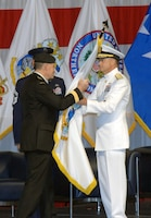 Canadian Gen. Walt Natynczyk, Chief of the Canadian Defence Staff, presents the North American Aerospace Defense flag to Navy Adm. James Winnefeld, NORAD and U.S. Northern Command commander, during the commands' change of command ceremony at Peterson Air Force Base May 19.