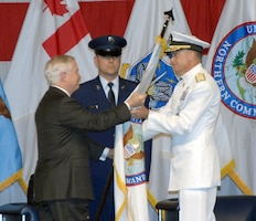Defense Secretary Robert Gates presents the U.S. Northern Command flag to Navy Adm. James Winnefeld, NORAD and U.S. Northern Command commander, during the commands' change of command ceremony at Peterson Air Force Base May 19.