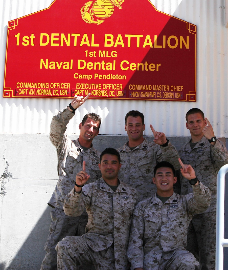 Top from left to right: Petty Officer 3rd Class Michael Conley, Petty Officer 3rd Class Joshua Fallick, and Petty Officer 3rd Class  Justin Redus. Bottom from left to right: Petty Officer 3rd Class Erik Bryar, Petty Officer 3rd Class Albert Vu, all hospital corpsmen  with 1st Dental Battalion, 1st Marine Logistics Group, and the winning team of the Corpsman Cup Challenge, pose in front of their  unit's sign.