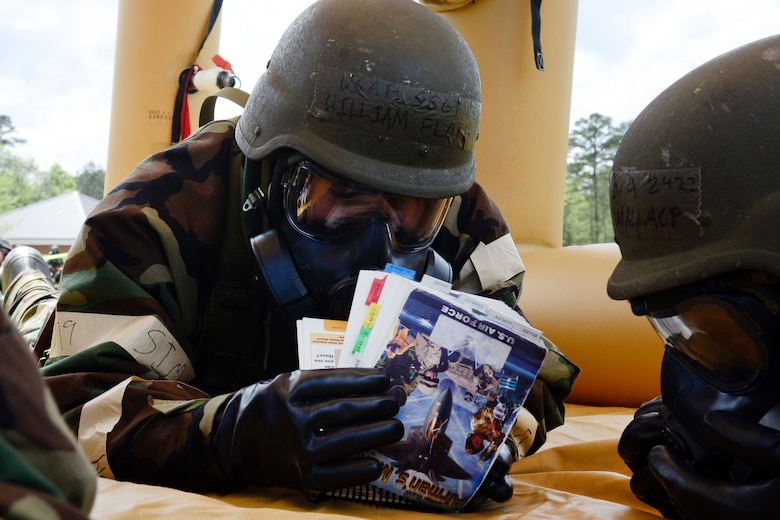 U.S. Air Force Staff Sgt. William Floyd, assigned to the 169th Fighter Wing of the South Carolina Air National Guard, reads his Airman's Manual during a simulated chemical attack during the 169th Fighter Wing Readiness Exercise, McEntire Joint National Guard Base, S.C., April 12, 2013. Members of the 169th Fighter Wing are preparing for a Phase I and II Readiness Inspection, which evaluates a unit's ability to deploy, then operate and launch missions in a chemical combat environment.  (U.S. Air National Guard photo by Staff Sgt. Jorge Intriago/Released)