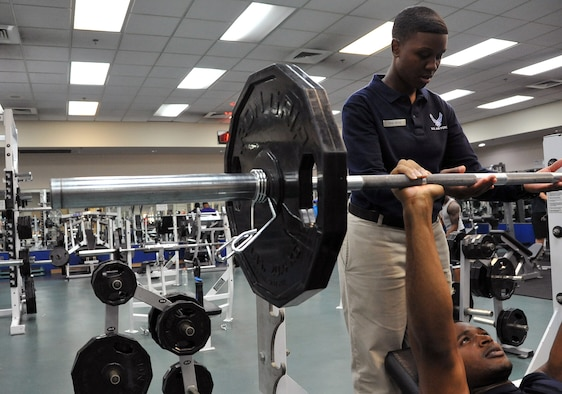 Senior Airman Raashida Wise, 51st Force Support Squadron fitness specialist, assists Capt. Ilechukwu Agu, 731st Air Mobility Squadron air freight officer in charge, at the fitness center on Osan Air Base, Republic of Korea, June 28, 2013 Osan fitness specialists are trained to ensure members are using proper form on gym equipment.  (U.S. Air Force photo/Senior Airman Kristina Overton)