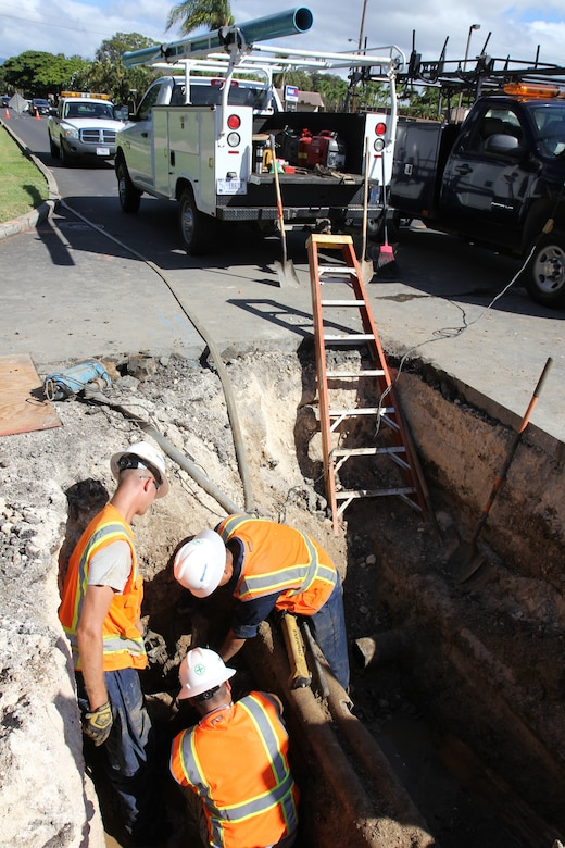 From left clockwise, Tech. Sgt. Benjamin M. Johnson, a plumber with the 647th Civil Engineering Squadron, and Airman 1st Class Robert T. Shikina and Senior Airman Tito M. Irlas plumbers with the 624th Civil Engineering Squadron, position a snap cutter on a water main pipe in order to remove the broken pipe and repair a leak, Joint Base Pearl Harbor-Hickam, Hawaii, June 27, 2013. Communication lines, center, can be seen running over the water main, as well as an abandoned fuel line, to the far right, creating obstacles. (U.S. Air Force photo by Tech. Sgt. Phyllis E. Keith)