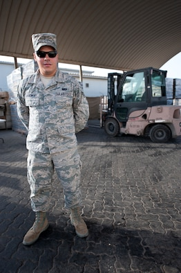 U.S. Air Force Airman 1st Class Mickey Laskowsky, 380th Expeditionary Force Support Squadron food services technician, poses for a photo in front of his 6K loader and a stockpile of water for the base at an undisclosed location in Southwest Asia July 3, 2013. Laskowsky is the main forklift operator for the 380th EFSS where he uses it to deliver water to 58 different stops a day. He is originally from Pittsburgh, Penn., and is stationed with the 171st Air Refueling Wing with the Pennsylvania Air National Guard. (U.S. Air Force photo by Senior Airman Jacob Morgan)