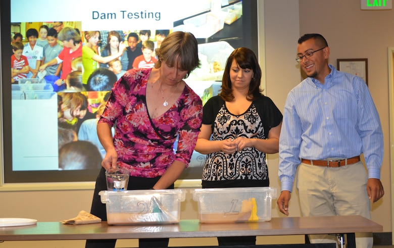 ALBUQUERQUE, N.M., -- Ariane Pinson, left, and Luis Pulido, Team III members, test different types of materials to determine how long and how well these materials hold up against water as part of their STEM presentation.