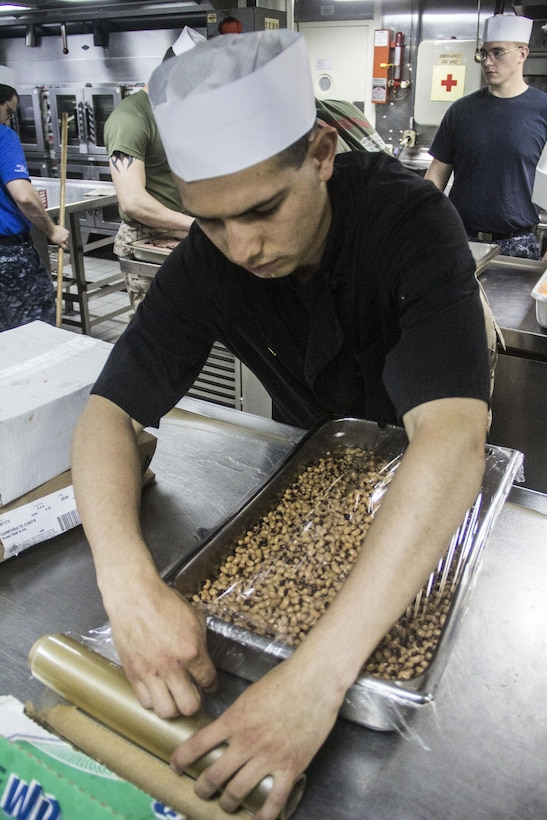 U.S. Marine Corps Lance Cpl. Alejandro Sanchez, food service specialist from Salinas, Calif., wraps a tray of beans aboard the USS Carter Hall (LSD 50) while at sea July 3, 2013. The 26th MEU is a Marine Air-Ground Task Force forward-deployed to the U.S. 5th Fleet area of responsibility aboard the Kearsarge Amphibious Ready Group serving as a sea-based, expeditionary crisis response force capable of conducting amphibious operations across the full range of military operations. (U.S. Marine Corps photo by Cpl. Michael S. Lockett/Released)