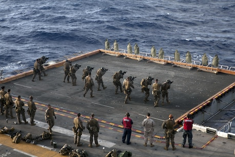 Marines and Sailors of the Force Reconnaissance Platoon, 31st Marine Expeditionary Unit, engage targets on the port side elevator of the ship here, July 7. The group used M4 carbines and M45 pistols to hone their skills in close combat marksmanship. The 31st MEU is the Marine Corps' force in readiness for the Asia Pacific region and the only continuously forward-deployed MEU.