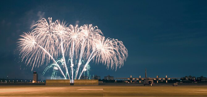 Fireworks light up the sky and a nearby C-130 on the flightline at Yokota Air Base, Japan, July 4, 2013 during the fourth of July celebration. The installation hosted a number of events throughout the day, which culminated with a performance by the Lt. Dan Band and the firework display to celebrate the holiday.  (U.S. Air Force photo by Senior Airman Michael Washburn/released)