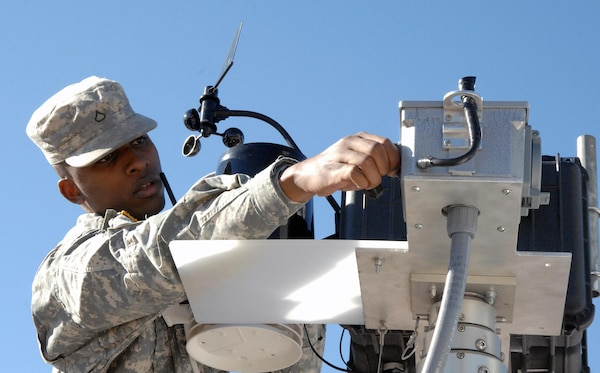 COLORADO SPRINGS, Colo. - Army Pfc. Aaron Garlington, 206th Army Liaison Team, sets up a portable cell phone tower and weather station during the Coalition Warrior Interoperability Demonstration June 15. CWID allows the military to test emerging technologies in an operational setting. U.S. Northern Command, in cooperation with the city of Colorado Springs, tested the new equipment in a scenario where terrorists destroyed several cell phone towers, and temporary communications needed to be reestablished quickly. (U.S. Air Force photo by Staff Sgt. Thomas J. Doscher)