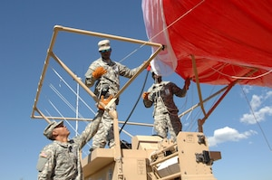 COLORADO SPRINGS, Colo. - Army Pvt. Sherman Huff, 207th Army Liaison Team, helps Army Pfc. Aaron Garlington, 206th Army Liaison Team, and Spc. Shaun Marshall, 207th ALT, inflate a helium-filled aerostat surveillance balloon during the Coalition Warrior Interoperablity Demonstration June 16. The goal of the demonstration was to have military members use and assess new technologies in operational conditions. Equipment tested included aerostat balloons and hand-held phones that could switch between cellular and satellite with the push of a button. (U.S. Air Force photo by Staff Sgt. Thomas J. Doscher)