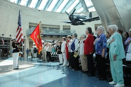 A group of retired female Marines faces a female color guard during the playing of the national anthem at the National Museum of the Marine Corps' dedication of its Molly Marine statue July 5, 2013.