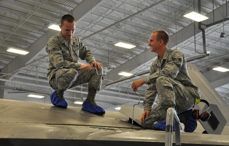 Senior Airman Christopher Dunn, 43rd Aircraft Maintenance Unit F-22 specialist and Airman 1st Class Kenan Harvey, 43rd AMU F-22 specialist, address an issue on top of an F-22 Raptor as part of Avionics Health of the Fleet inside the hangar of the 43rd AMU at Tyndall Air Force Base, Fla. AVHOF is a program implemented to increase the number of fully mission capable F-22s on Tyndall's flight line. (U.S. Air Force photo by Airman 1st Class Alex Echols)