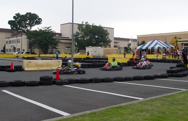 YOKOTA AIR BASE, Japan -- Adults and children drive go-carts during the Celebrate America festival at Yokota Air Base, Japan, July 4, 2013. The festivities also included free food, carnival games, bouncy castles and a petting zoo. (U.S. Air Force photo by Senior Airman Andrea Salazar/Released)