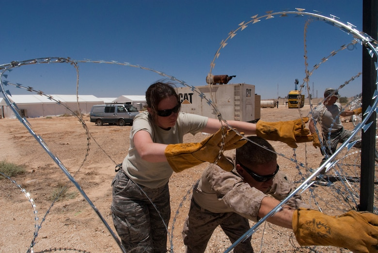 Technical Sgt. Sarah McCann, a quality assurance specialist from the 140th Wing, Colorado Air National Guard, installs Constantine wire with a Marine from VMFA-115, for a defensive perimeter at a training base in Northern Jordan as part of the Eager Lion exercise. Eager Lion is a U.S. Central Command-directed, irregular warfare-themed exercise focusing on missions the United States and its coalition partners might perform in support of global contingency operations. (U.S. Air National Guard photo by Senior Master Sgt. John P. Rohrer)