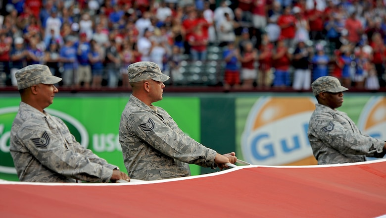U.S. Air Force Tech. Sgt. Craig Cooper, 7th Civil Engineer Squadron, Dyess Air Force Base, Texas, center, holds an American flag July 4, 2013, at Rangers Ballpark in Arlington, Texas during his stepdaughter's Air Force enlistment ceremony, prior to a Texas Ranger's baseball game. (U.S. Air Force photo by Airman 1st Class Peter Thompson/Released)