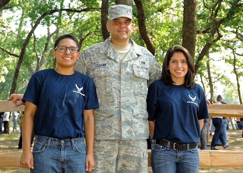 U.S. Air Force Tech. Sgt. Craig Cooper, 7th Civil Engineer Squadron, Dyess Air Force Base, Texas, stands with his stepdaughters Elizabeth Martinez, left, and Katherine Martinez July 4, 2013, outside of Rangers Ballpark in Arlington, Texas. Cooper and his daughters traveled to Arlington to participate in an Air Force enlistment ceremony on the Texas Rangers' baseball field. (U.S. Air Force photo by Airman 1st Class Peter Thompson/Released)