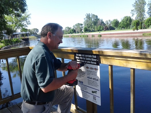 FORMER WURTSMITH AIR FORCE BASE, Mich. -- Dave Strainge, Air Force Civil Engineer Center environmental coordinator for the former Wurtsmith Air Force Base, puts up a fishing advisory sign June 26, 2013, on the AuSable River. The signage is one of the ways AFCEC is working with state health and environmental agencies to inform residents of the presence of perflourinated compounds, an emerging contaminant found in fish samples taken from the river in 2012. The center works closely with the Environmental Protection Agency and the Michigan Department of Environmental Quality to ensure environmental cleanup activities satisfy all regulatory standards while protecting human health and the environment. Strainge is a member of the AFCEC Installations Directorate base realignment and closure program management division. (Courtesy photo)
