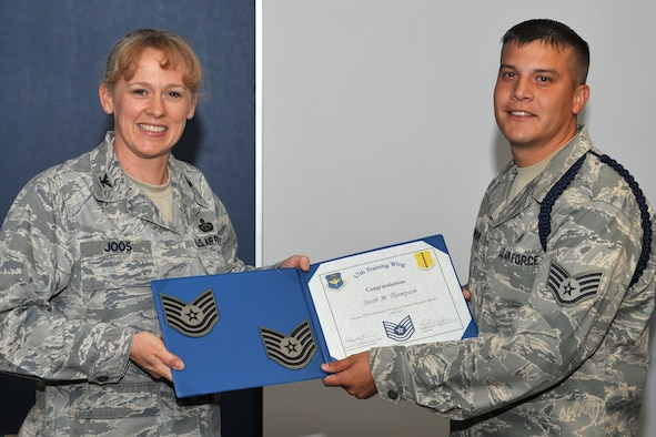 GOODFELLOW AIR FORCE BASE, Texas-- Col. Kimberlee Joos, 17th Training Wing Commander, presents Staff Sgt. Jacob Thompson, 316th Training Squadron military training leader, with his Stripes for Exceptional Performers certificate for Technical Sergeant at the 316th TRS dormitory building June 2. The STEP promotion program offers commanders a limited opportunity to immediately promote enlisted members to staff sergeant, technical sergeant or master sergeant. (U.S. Air Force photo/Senior Airman Michael Smith)