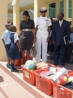 Two Bahamian students greet U.S. Ambassador Nicole Avant, Navy Lt. Cmdr. Janice Smith and Howard Newbold, District Superintendent for the North Western District, on arrival at Woodcock Primary School Sept. 9. U.S. Northern Command funded $6,000 in school supplies for local schools as part of its longstanding partnership with the people of The Bahamas and demonstrates the Department of Defense's commitment to helping to strengthen communities and build partnerships around the world.