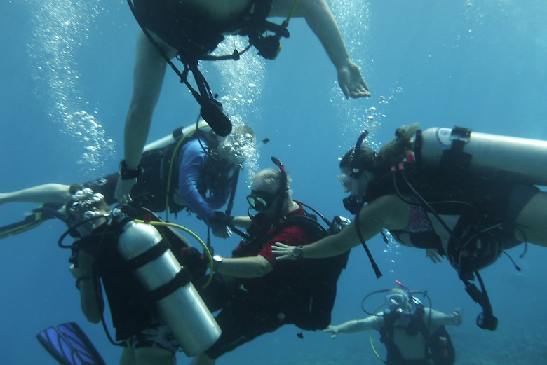 Bob Clark, 36th Force Support Squadron Andersen Family Dive Center instructor, teaches diving students during an advanced diving class in the Pacific Ocean, July 7, 2013. The Family Dive Center offers four main certification classes and 10 specialty courses. Anyone ages 8 and up can learn to dive. (U.S. Air Force photo by Staff Sgt. Veronica Montes/Released)