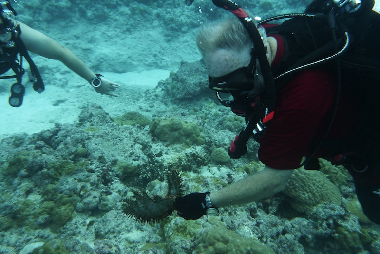 Bob Clark, 36th Force Support Squadron Andersen Family Dive Center instructor, shows students sea life during an advanced diving class in the pacific ocean, July 7, 2013. With more than 75 dive spots around Guam, the Andersen Dive Center offers weekend group dives people can sign up for. (U.S. Air Force photo by Staff Sgt. Alexandre Montes/Released)